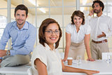 Smiling young businesswoman with colleagues at office