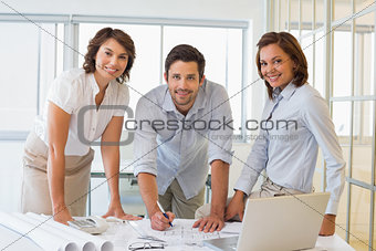 Smiling business people working on blueprints at office