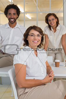 Smiling businesswoman with colleagues at office