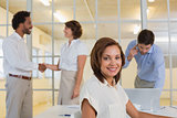 Smiling businesswoman with colleagues shaking hands at office