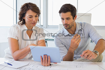 Business people looking at digital tablet in office