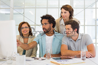 Business people using computer together at office desk