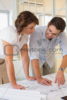 Business people working on blueprints at office