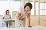 Businesswoman working on blueprints with colleague in background at office