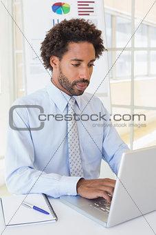 Businessman using laptop at office desk