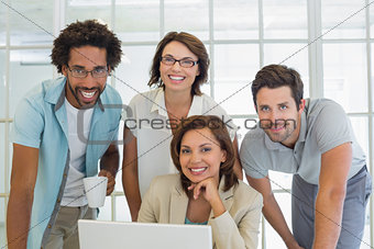 Smiling business people using laptop at office