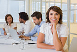 Smiling businesswoman with colleagues in meeting at office