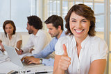 Smiling businesswoman gesturing thumbs up with colleagues in meeting at office