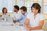 Businesswoman writing notes with colleagues in meeting at office