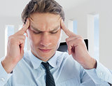 Composite image of businessman with a headache