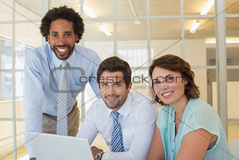 Three business people using laptop together at office