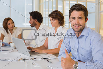 Smiling businessman gesturing thumbs up with colleagues in meeting