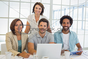 Smiling business people using laptop together at office