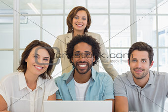 Portrait of smiling business people using laptop