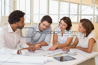 Colleagues working on blueprints in office
