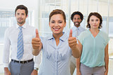 Businesswoman with colleagues gesturing thumbs up