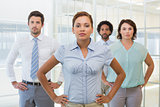 Serious businesswoman standing with colleagues