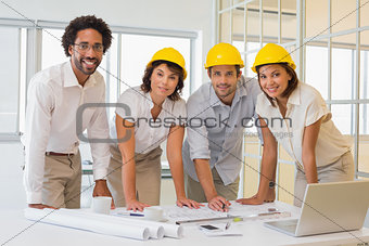 Smiling colleagues working on blueprints at office