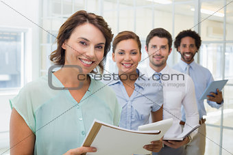 Business colleagues holding notepads in row at office