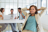 Relaxed businesswoman with colleagues in meeting at office