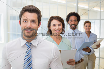 Business colleagues holding notepads in row