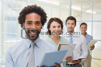 Business colleagues holding notepads and digital tablet in row
