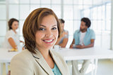Close-up of smiling businesswoman with colleagues in meeting