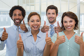 Business colleagues gesturing thumbs up