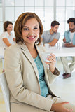 Smiling businesswoman having coffee with colleagues in meeting