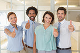 Business colleagues gesturing thumbs up in office