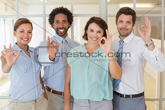 Business colleagues gesturing okay sign in office