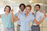 Cheerful business colleagues cheering in office