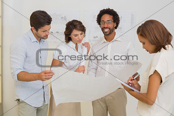 Business colleagues working on blueprints