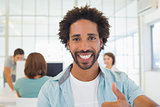 Businessman gesturing thumbs up with colleagues in meeting