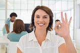 Smiling businesswoman gesturing ok sign with colleagues in meeting