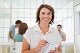 Businesswoman writing notes up with colleagues in meeting