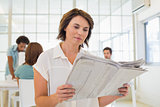 Businesswoman reading newspaper with colleagues in meeting