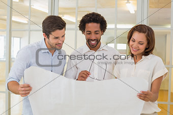 Business colleagues working on blueprints at office