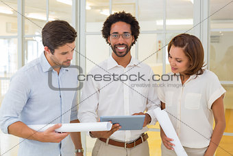 Business colleagues using digital tablet with blueprints