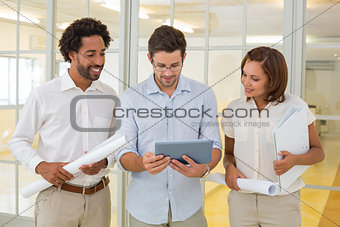 Business colleagues using digital tablet with blueprints in office
