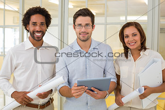 Business colleagues with blueprints and digital tablet in office