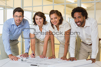 Smiling business colleagues working on blueprints