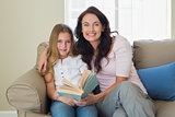 Mother and daughter holding book on sofa
