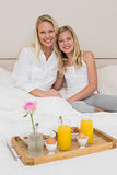 Mother and daughter breakfast tray on bed