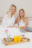 Mother and daughter with croissant on bed