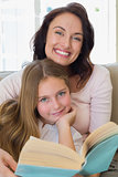 Woman and daughter with book at home