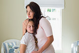 Woman embracing little daughter in house