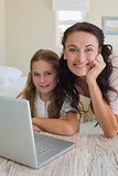 Girl and mother with laptop at table