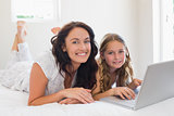 Mother and daughter with laptop lying in bed