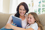 Mother and daughter using digital tablet in house